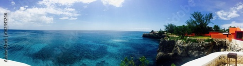 Plexiglas Groen blauw Panoramic view from Negril, Jamaica (Caribbean island): turquoise blue ocean, sky with white clouds, palm trees, stone wall and red house create a beautiful summer vacation