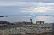 Newfoundland: Young female tourist admiring iceberg in a calm northern bay
