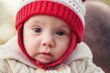 Closeup portrait of cute adorable white Caucasian smiling baby girl boy with large brown eyes in red knitted hat  looking in camera