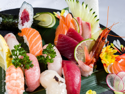 Fototapeta Close up of a mixed sushi and sashimi on a black dish