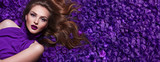 The girl in the petals. Beautiful young girl lies in the violet petals in a long dress. Glamor, luxe. Hair - curls. Makeup - arrows, purple lipstick. Love, romance. - 162490201
