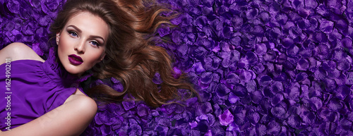 Foto Murales The girl in the petals. Beautiful young girl lies in the violet petals in a long dress. Glamor, luxe. Hair - curls. Makeup - arrows, purple lipstick. Love, romance.