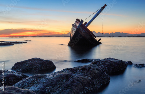 Deurstickers Schipbreuk An old shipwreck or abandoned shipwreck taken during a beautiful sunset , Wrecked boat abandoned stand on beach or Shipwrecked off the coast of Thailand.
