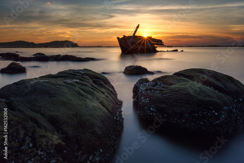 Foto op Aluminium Schipbreuk An old shipwreck or abandoned shipwreck taken during a beautiful sunset , Wrecked boat abandoned stand on beach or Shipwrecked off the coast of Thailand.