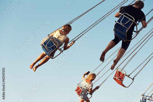 Fotobehang Amusementspark Young people on a whirligig in amusement park.