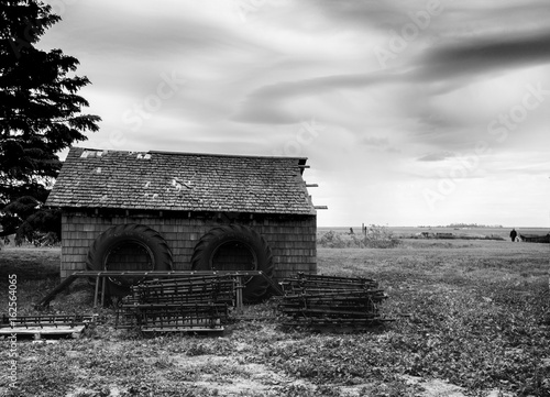 black and white tractor tires on an old farm house in green fields: