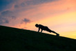 Silhouette of man doing push up outdoors.