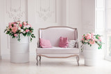 Interior of a snow-white living room with a vintage sofa and flowers - 162600699