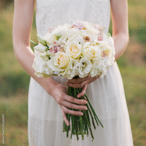 bride in a dress standing in a green garden and holding a wedding bouquet of flowers and greenery. Woman holding colorful bouquet with her hands on wedding day
