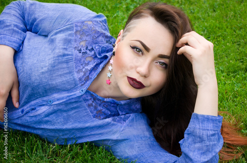 Portrait of a beautiful young brunette girl on a green grass Poster