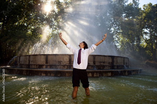 Excited businessman standing in fountain.