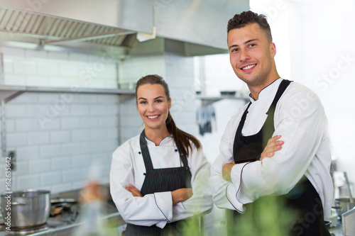 Two smiling chefs in kitchen