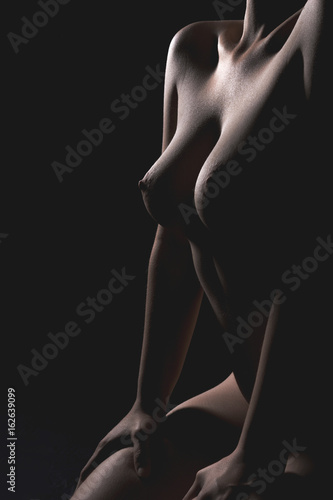 Beautiful naked female body on black background.