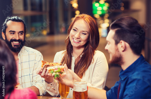 friends eating pizza with beer at restaurant - 162646401