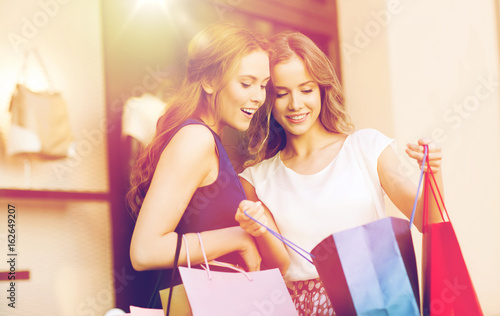 happy women with shopping bags at shop window