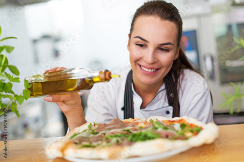 Smiling chef preparing pizza in kitchen