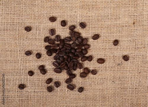 pile coffee beans on jute, linen background and texture, top view