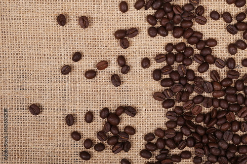 Tuinposter Koffiebonen pile coffee beans on jute, linen background and texture, top view