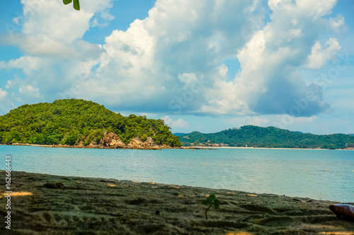 Shaded beach extending into a blue ocean and a tree covered island. Framed by a bright blue cloudy sky