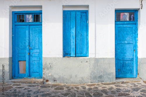 Blue door in traditional house in historic village of Tripiti on Milos island. Cyclades, Greece.