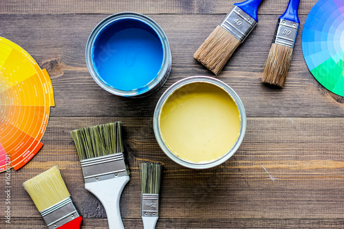 Colorful paints and brushes on grey wooden desk background top view