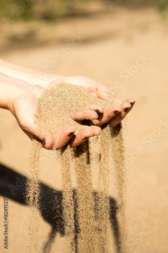 sand running through hands of woman Poster