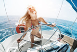 Young happy woman steering sailing boat in a tropical sea - 162723404