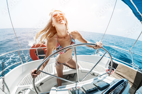Fotobehang Zeilen Young happy woman steering sailing boat in a tropical sea