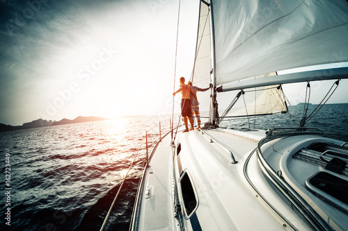 Fotobehang Zeilen Young couple enjoys sunset from the sailing boat moving in the tropical sea