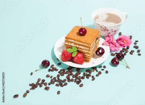 Tasty piece of cake on the white plate and cup of coffee,decorated with flowers,coffee beans,strawberries and cherry on the light mint background with empty place,perspective view,diagonal composition © alchena