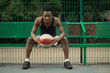 Portrait of african american man sitting on basketball court