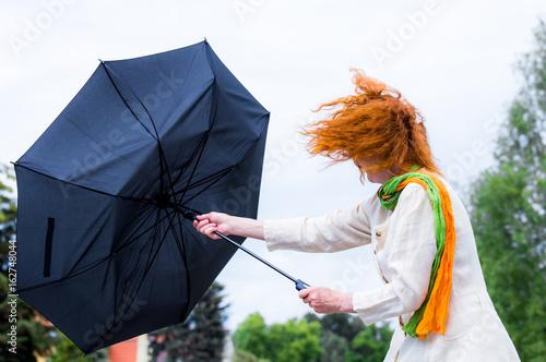 eine Frau mit roten Haaren versucht ihren Regenschirm festzuhalten