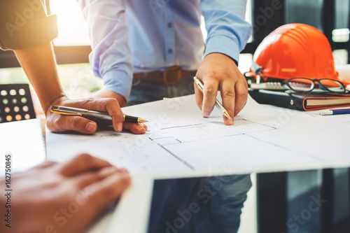 Architecture engineering teamwork meeting at workplace to plan drawing a new blueprint busy working hard for apartment building small business of their customer service.