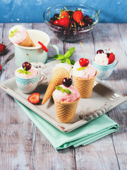 Home made strawberry and cherry ice cream served in waffle cups and cones on a ceramic tray. Vintage mood