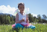 Girl playing with dandelion flower