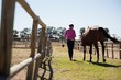 Rear view of woman walking with horse at ranch - 162769832