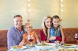Portrait of cheerful family with children at restaurant