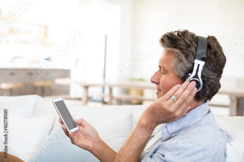 Man listening to music on headphones in living room