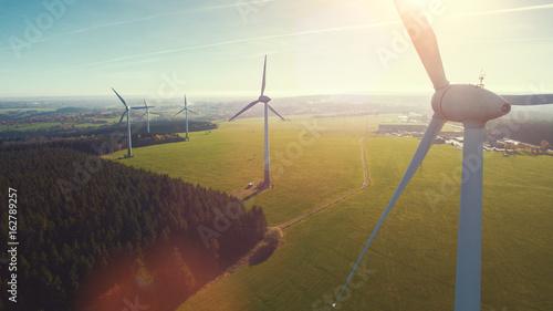 Leinwanddruck Bild Windmill at windfarm on a sunny summer day