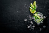 Lime and Mint cocktail, with ice, on a black wooden surface. Top view. Free space. - 162801083