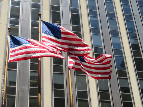 American flags flying in front of a skyscraper Poster