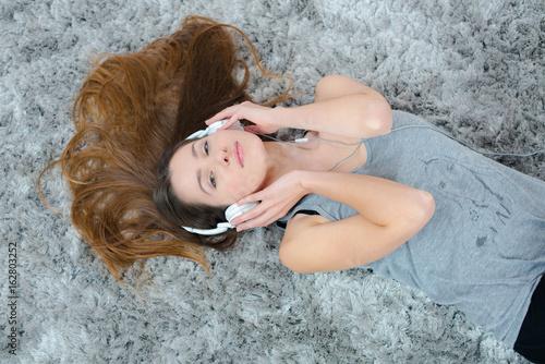 Plakát Woman layed on carpet listening to headphones