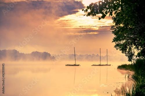 Morning foggy lake landscape. Boats on the lake.
