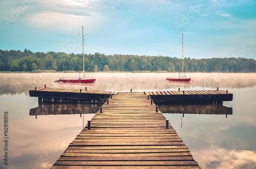 rano-mglisty-krajobraz-jeziora-drewniany-molo-i-lodzie-na-jeziorze