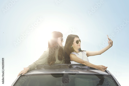 Two women with smartphone on car roof