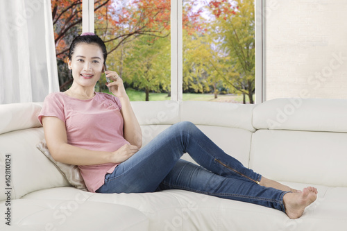 Woman speaking on mobile phone on couch