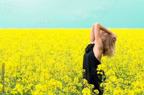 Beautiful girl in yellow flowers against the blue sky