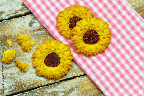 Crunchy cookies with strawberry jam on pink cloth and wooden surface