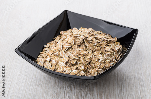 Dry rye flakes in black bowl on table