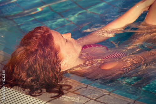 redhead freckled young woman in pool real people concept